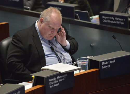 """Mayor Rob Ford speaks on a cell phone at city council in Toronto on Wednesday, Nov. 13, 2013. Almost every member of Toronto's City Council stood up and asked Mayor Rob Ford to take a leave of absence during a city council meeting Wednesday after he admitted smoking crack last week.""""Together we stand to ask you to step aside and take a leave of absence,"""" Councilor Jaye Robinson said, reading open letter to Ford in City Council. The council voted 41-2 to accept the letter Wednesday, with the embattled mayor casting one of the opposing votes. (AP Photo/The Canadian Press, Nathan Denette)"""