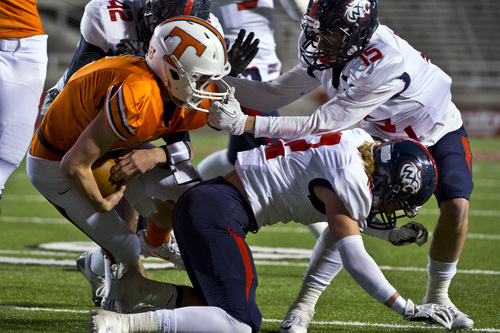 Chris Detrick     The Salt Lake Tribune Timpview's Britain Covey (2) is face masked by Woods Cross's Kyle Easton (15) during the game at Rice-Eccles Stadium Thursday November 14, 2013. Timpview is winning the game 23-6 at halftime.