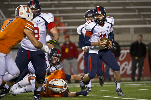 Chris Detrick     The Salt Lake Tribune Woods Cross's Clay Kidman (11) scrambles away from Timpview's TJ Anderberg (72) during the game at Rice-Eccles Stadium Thursday November 14, 2013. Timpview defeated Woods Cross 37-6.