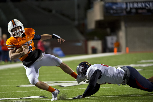 Chris Detrick     The Salt Lake Tribune Timpview's Britain Covey (2) is tackled by Woods Cross's Deion Saumalu (42) during the game at Rice-Eccles Stadium Thursday November 14, 2013. Timpview defeated Woods Cross 37-6.