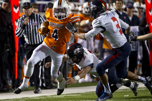 Chris Detrick     The Salt Lake Tribune Timpview's Porter Case (4) is tackled by Woods Cross's Danny Fiefia (7) and Woods Cross's Xequille Harry (3) during the game at Rice-Eccles Stadium Thursday November 14, 2013. Timpview defeated Woods Cross 37-6.