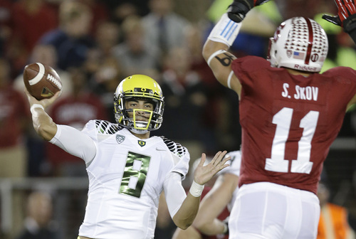Oregon quarterback Marcus Mariota (8) passes as Stanford linebacker Shayne Skov (11) defends during the first quarter of of an NCAA college football game in Stanford, Calif., Thursday, Nov. 7, 2013. (AP Photo/Marcio Jose Sanchez)