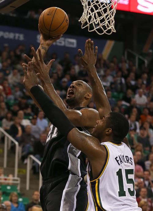 San Antonio Spurs Tim Duncan, top, shoots over Utah Jazz's Derrick Favors during the first half of an NBA basketball game in Salt Lake City, Friday, Nov. 15, 2013. (AP photo/George Frey)
