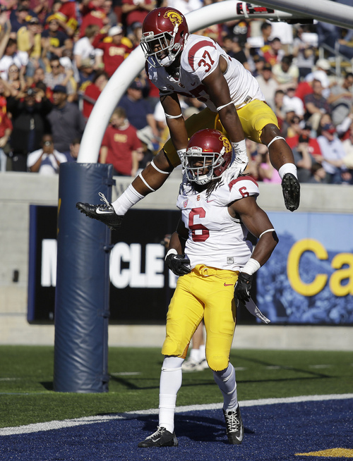 Southern California safety Josh Shaw, bottom, is greeted by teammate Javorius Allen after scoring a 14-yard touchdown following a California punt that was blocked during the second quarter of an NCAA college football game Saturday, Nov. 9, 2013, in Berkeley, Calif. (AP Photo/Eric Risberg)