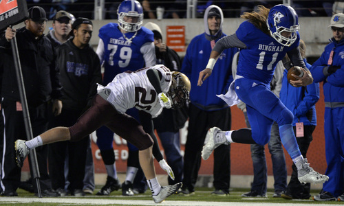 Chris Detrick  |  The Salt Lake Tribune Bingham's Kade Jensen (11) is pushed out of bounds by Lone Peak's Benson Lewis (20) during the 5A semifinal game at Rice-Eccles Stadium Friday November 15, 2013. Bingham defeated Lone Peak 48-13.