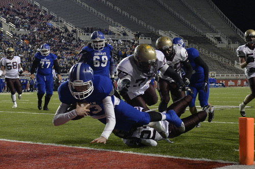 Chris Detrick  |  The Salt Lake Tribune Bingham's Kyle Gearig (13) scores a touchdown past Lone Peak's Chase Armstrong (22) and Lone Peak's Josh Southwick (77) during the 5A semifinal game at Rice-Eccles Stadium Friday November 15, 2013.