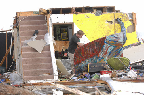 A Washington homeowner moves debris next to a set of stairs that once led to the second floor of his home in Washington, Ill., Sunday, Nov. 17, 2013. Intense thunderstorms and tornadoes swept across the Midwest, causing extensive damage in several central Illinois communities while sending people to their basements for shelter. (AP Photo/The Pantagraph, Steve Smedley)
