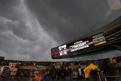 Fans are advised to leave the stadium as severe weather passes over Soldier Field during the first half of an NFL football game between the Chicago Bears and the Baltimore Ravens, Sunday, Nov. 17, 2013, in Chicago. (AP Photo/Charles Rex Arbogast)