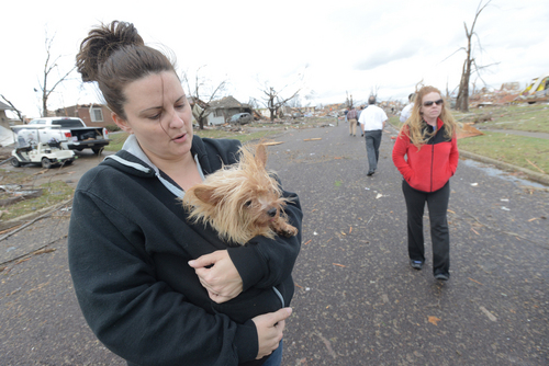 Aimee Royer holds a dog she rescued from debris after a Sunday morning tornado sliced through a subdivision on the North side of Washington, Ill., Sunday, Nov. 17, 2013. Royer and her friend, Kendra Gray, at right, said their home was spared. Several homes are cleared down to the foundation. Intense thunderstorms and tornadoes swept across the Midwest, causing extensive damage in several central Illinois communities while sending people to their basements for shelter. (AP Photo/The Pantagraph, Steve Smedley)