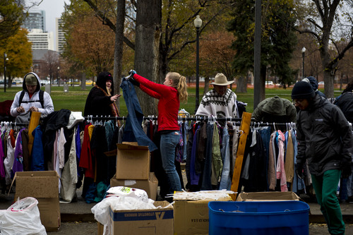 """Chris Detrick     The Salt Lake Tribune A red-coated volunteer with The Legacy Initiative holds up a pair of pants to helps a needy person check their size during a """"Street Boutique"""" Saturday at Pioneer Park. About 100 volunteers gave out clothing, burritos and bottled water to homeless people downtown."""