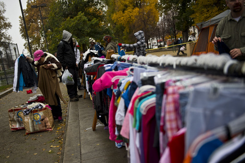 """Chris Detrick     The Salt Lake Tribune People look through racks of free clothes Saturday in Pioneer Park, where a nonprofit group, The Legacy Initiative, continued its homeless outreach with a """"Street Boutique"""" and deliveries of homemade bean-and-cheese burritos. (Nov. 16, 2013)."""