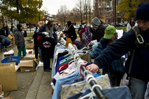 """Chris Detrick     The Salt Lake Tribune People look through racks of free clothes Saturday in Pioneer Park, where a nonprofit group, The Legacy Initiative, continued its homeless outreach with a """"Street Boutique"""" and deliveries of homemade bean-and-cheese burritos."""