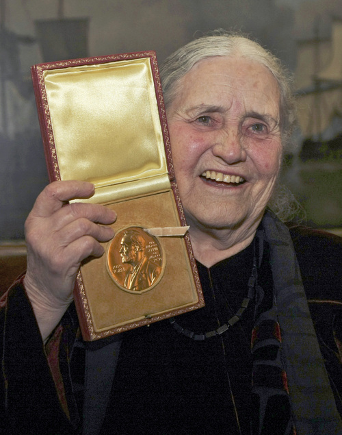 "FILE - In this Wednesday, Jan. 30, 2008 file photo, Nobel literature laureate, Doris Lessing holds up the 2007 Nobel Prize for Literature medal after being presented it by the Ambassador of Sweden, Staffan Carlsson, during a ceremony at the Wallace Collection art gallery in London. Doris Lessing, the free-thinking, world-traveling, often-polarizing writer of ""The Golden Notebook"" and dozens of other novels that reflected her own improbable journey across the former British empire, has died, early Sunday, Nov. 17, 2013.  She was 94. The author of more than 50 works of fiction, nonfiction and poetry, Lessing explored topics ranging from colonial Africa to dystopian Britain, from the mystery of being female to the unknown worlds of science fiction. (AP Photo/Matt Dunham, File)"