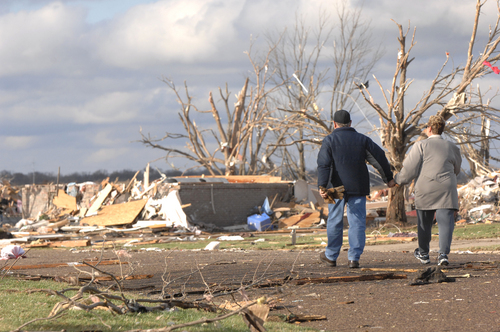 A couple walks down a street in the Devonshire subdivision on the North side of Washington, Ill., Sunday, Nov. 17, 2013. Intense thunderstorms and tornadoes swept across the Midwest, causing extensive damage in several central Illinois communities while sending people to their basements for shelter. (AP Photo/The Pantagraph, Steve Smedley)