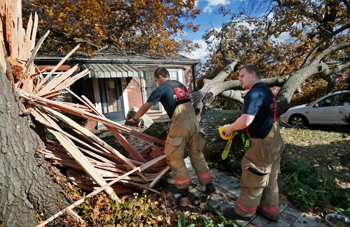 Webster Groves firefighters Chris Manita, center, and Matt Grossenhieder climb over a tree that fell on a house on Clydehurst Drive in Webster Groves, Mo., Sunday, Nov. 17, 2013.  The residents of the house were home at the time the tree fell but were not injured. Intense thunderstorms and tornadoes swept across a number of Midwestern states Sunday, causing damage in several central Illinois communities while sending people to their basements for shelter and even prompting officials at Soldier Field in Chicago to evacuate the stands and delay the Bears game.   (AP Photo/St. Louis Post-Dispatch, David Carson)  EDWARDSVILLE INTELLIGENCER OUT; THE ALTON TELEGRAPH OUT