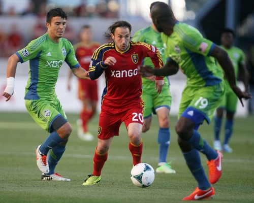 Kim Raff  |  The Salt Lake Tribune (middle) Real Salt Lake midfielder Ned Grabavoy (20) tries to break free as (left) Seattle Sounders FC midfielder Servando Carrasco (23) and (right)  Seattle Sounders FC defender Djimi Traore (19) defend during the first half of a game at Rio Tinto Stadium in Sandy on June 22, 2013.
