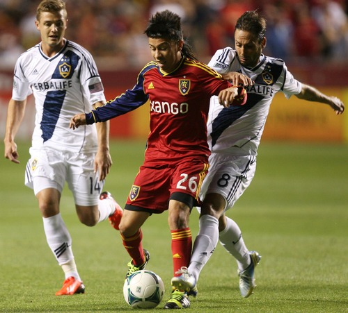 Kim Raff  |  The Salt Lake Tribune (left) Real Salt Lake midfielder Sebastian Velasquez (26) tries to hang onto the ball as (right) Los Angeles Galaxy midfielder Marcelo Sarvas (8) defends during the second half at Rio Tinto Stadium in Salt Lake City on June 8, 2013.  Real went on to win the game 3-1.