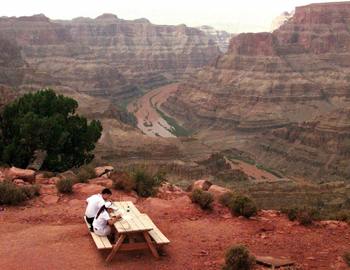 FILE - In this Sept. 2, 1998 file photo, a couple enjoy lunch on one of the scenic points at Grand Canyon West on the Hualapai Indian reservation in Arizona. A new study published in the journal Science Thursday, Nov. 29, 2012, suggests the western Grand Canyon formed 70 million years ago.  Some scientists disagree and believe the canyon was mainly carved by the Colorado River in the past 5 to 6 million years. (AP Photo/Jeff Robbins, File)