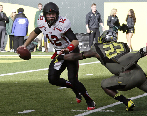 Utah quarterback Adam Schulz, left, is sacked by Oregon defender Derrick Malone, Jr., during the first half of an NCAA college football game  in Eugene, Ore., Saturday, Nov. 16, 2013. (AP Photo/Don Ryan)
