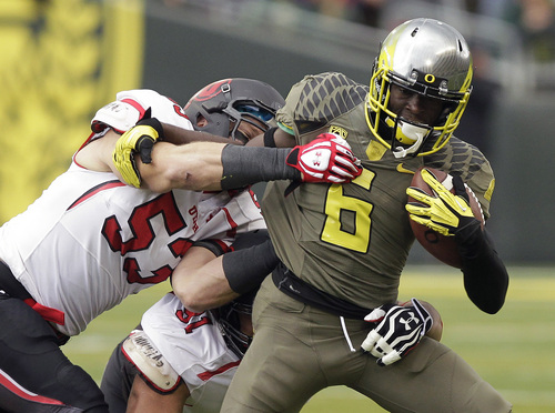 Oregon running back DeAnthony Thomas, right, struggles for yardage against Utah defenders Jason Whittingham, left, and Tenny Palepoi during the first half of an NCAA college football game  in Eugene, Ore., Saturday, Nov. 16, 2013. (AP Photo/Don Ryan)