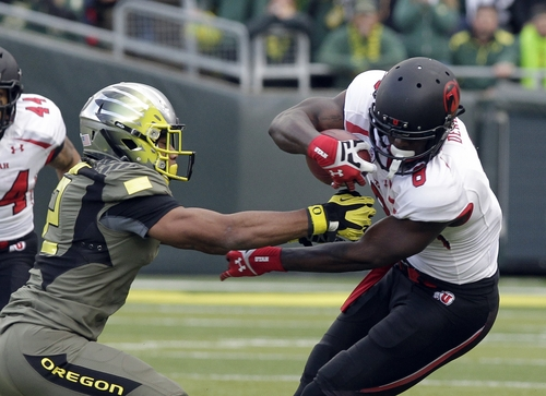 Utah receiver Anthony Denham, right, tries to evade Oregon defender Brian Jackson during the first half of an NCAA college football game  in Eugene, Ore., Saturday, Nov. 16, 2013. (AP Photo/Don Ryan)