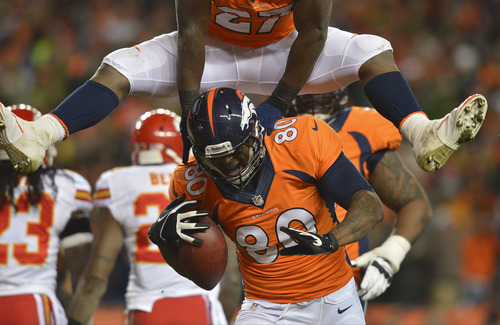 Denver Broncos running back Knowshon Moreno (27) leaps over Denver Broncos tight end Julius Thomas (80) after Thomas caught a touchdown pass against the Kansas City Chiefs in the first quarter of an NFL football game, Sunday, Nov. 17, 2013, in Denver. (AP Photo/Jack Dempsey)