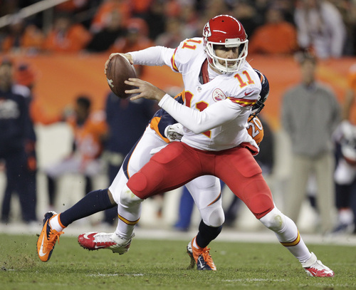 Kansas City Chiefs quarterback Alex Smith (11) slips away from Denver Broncos strong safety Mike Adams (20) in the second quarter of an NFL football game, Sunday, Nov. 17, 2013, in Denver. (AP Photo/Joe Mahoney)