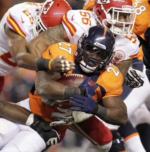 Denver Broncos running back Knowshon Moreno (27) is tackled by Kansas City Chiefs inside linebacker Derrick Johnson (56) in the first quarter of an NFL football game, Sunday, Nov. 17, 2013, in Denver. (AP Photo/Joe Mahoney)