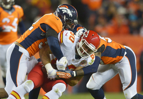 Kansas City Chiefs tight end Anthony Fasano (80) is tackled by Denver Broncos middle linebacker Wesley Woodyard (52) and outside linebacker Danny Trevathan (59) in the second quarter of an NFL football game, Sunday, Nov. 17, 2013, in Denver. (AP Photo/Jack Dempsey)