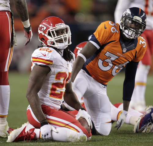 Kansas City Chiefs running back Jamaal Charles (25) looks up after being tackled by Denver Broncos cornerback Kayvon Webster (36) in the second quarter of an NFL football game, Sunday, Nov. 17, 2013, in Denver. (AP Photo/Joe Mahoney)