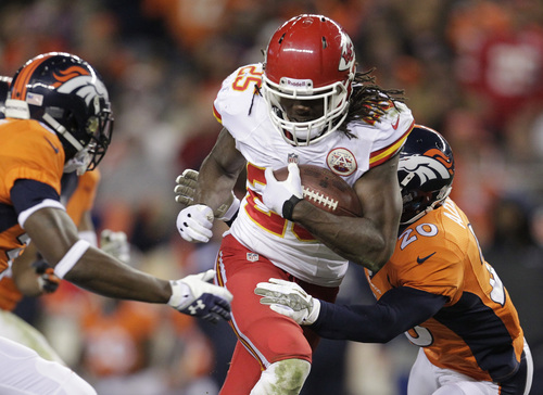 Kansas City Chiefs running back Jamaal Charles (25) runs the ball against Denver Broncos strong safety Mike Adams (20) and cornerback Kayvon Webster (36) in the third quarter of an NFL football game, Sunday, Nov. 17, 2013, in Denver. (AP Photo/Joe Mahoney)