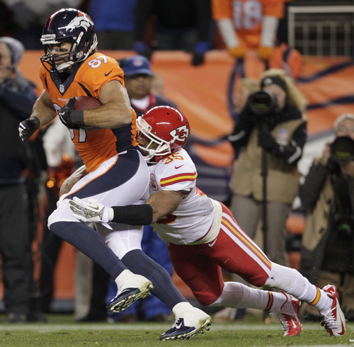 Denver Broncos wide receiver Eric Decker (87) is wrapped up by Kansas City Chiefs defensive back Quintin Demps (35) in the third quarter of an NFL football game, Sunday, Nov. 17, 2013, in Denver. (AP Photo/Joe Mahoney)