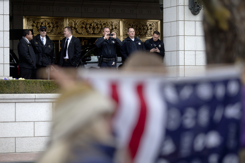 Jim McAuley | The Salt Lake Tribune Security and police personnel take cell phone photoso of the protest forming against the Trans-Pacific Partnership talks at the Grand America Hotel in Salt Lake City on Tuesday, November 19, 2013.