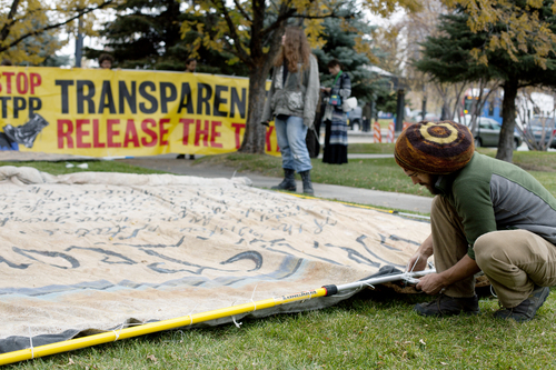 Jim McAuley | The Salt Lake Tribune Eric Ross of the Backbone Campaign prepares the finishing touches on signs to protest the Trans-Pacific Partnership talks outside of the Grand American Hotel in Salt Lake City on Tuesday, November 19, 2013.