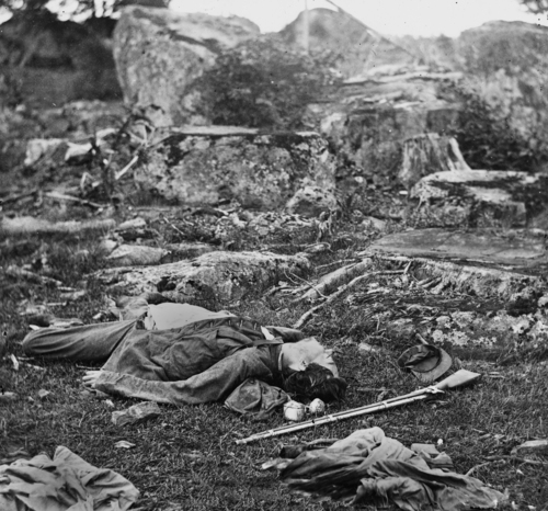 """In this photo provided by the Library of Congress, a dead Confederate soldier lies in """"the devil's den"""" in Gettysburg, Pa., following the Battle of Gettysburg during the Civil War, July 5, 1863. (AP Photo/Library of Congress/Alexander Gardner)"""