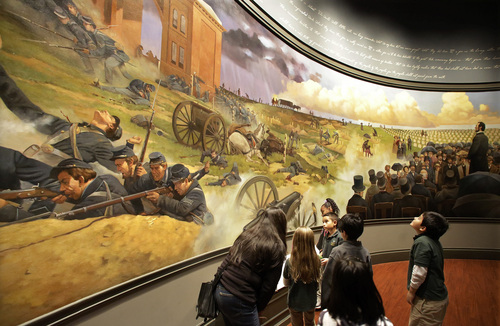 In this Friday, Nov. 15, 2013 photo, school groups and visitors view the Gettysburg Address and battle mural at the Abraham Lincoln Presidential Museum and Library , in Springfield, Ill. (AP Photo/Seth Perlman)
