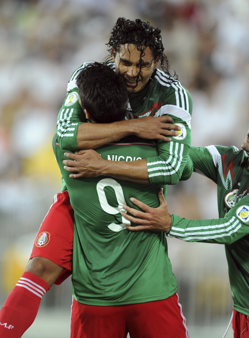 Mexico's Carlos Pena, top, is hugged by Aldo de Nigris after scoring against New Zealand in the World Cup soccer qualifier at Westpac Stadium in Wellington, New Zealand, Wednesday, Nov. 20, 2013. (AP Photo/SNPA, Ross Setford) NEW ZEALAND OUT