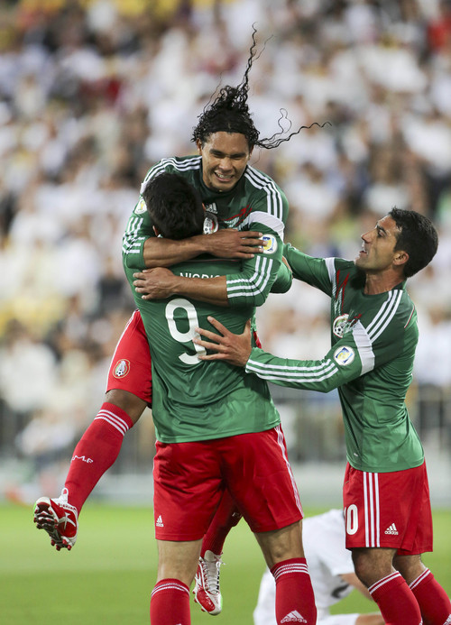 Mexico's Carlos Pena, top, is hugged by Aldo de Nigris after scoring a goal against New Zealand in their World Cup qualifying soccer match at Westpac Stadium in Wellington, New Zealand, Wednesday, Nov. 20, 2013. (AP Photo/SNPA, John Cowpland) NEW ZEALAND OUT