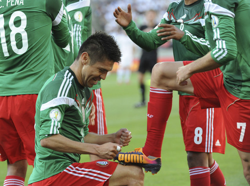 Mexico's Oribe Peralta performs to polish a shoe of teammate Miguel Layun after scoring a goal against New Zealand in their World Cup qualifying soccer match at Westpac Stadium in Wellington, New Zealand, Wednesday, Nov. 20, 2013. (AP Photo/SNPA, John Cowpland) NEW ZEALAND OUT