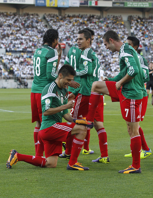 Mexico's Oribe Peralta, left in foreground, celebrates after scoring a goal against New Zealand in their World Cup qualifying soccer match at Westpac Stadium in Wellington, New Zealand, Wednesday, Nov. 20, 2013. (AP Photo/SNPA, John Cowpland) NEW ZEALAND OUT
