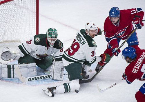 Minnesota Wild's Nate Prosser (39) blocks a shot from Montreal Canadiens' David Desharnais, right, as Wild's goaltender Josh Harding, left, and Canadiens' Brendan Gallagher look on during the first period of an NHL hockey game, Tuesday, Nov. 19, 2013 in Montreal. (AP Photo/The Canadian Press, Graham Hughes)