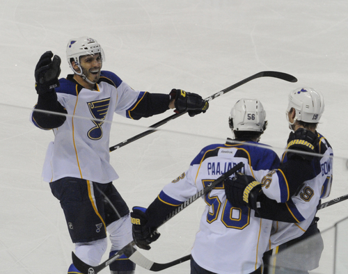 St. Louis Blues'  Maxim Lapierre, left, joins  Jay Bouwmeester, right to celebrate a goal by Magnus Paajarvi, center, of Sweden, during the third period of an NHL hockey game against Buffalo Sabres in Buffalo, N.Y., Tuesday, Nov. 19, 2013.  St. Louis won 4-1. (AP Photo/Gary Wiepert)
