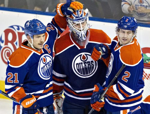 Edmonton Oilers' Andrew Ference (21), goalie Devan Dubnyk (40) and Jeff Petry (2) celebrate the 7 to 0 win over the Columbus Blue Jackets during NHL hockey action in Edmonton, Alberta Tuesday Nov. 19, 2013. (AP Photo/The Canadian Press, Jason Franson)