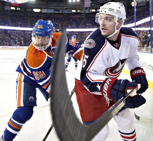 Columbus Blue Jackets' Mark Letestu (55) and Edmonton Oilers' Sam Gagner (89) battle in the corner during the first period of an NHL hockey game, Tuesday, Nov. 19, 2013 in Edmonton, Alberta. (AP Photo/The Canadian Press, Jason Franson)