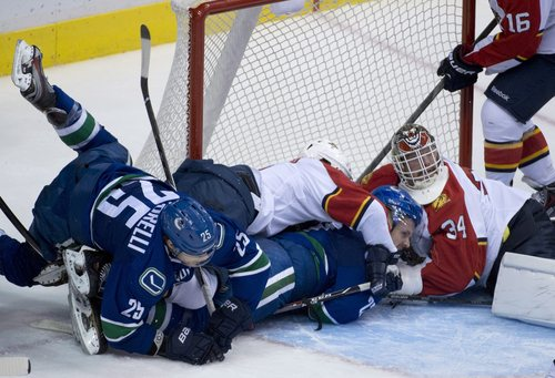 Florida Panthers center Jonathan Huberdeau (11) tries to clear Vancouver Canucks left wing Daniel Sedin (22) from in front of Florida Panthers goalie Tim Thomas (34) as Vancouver Canucks center Mike Santorelli (25) falls into the goal crease during third period NHL action in Vancouver, British Columbia, Tuesday, Nov. 19, 2013.   (AP Photo/The Canadian Press, Jonathan Hayward)