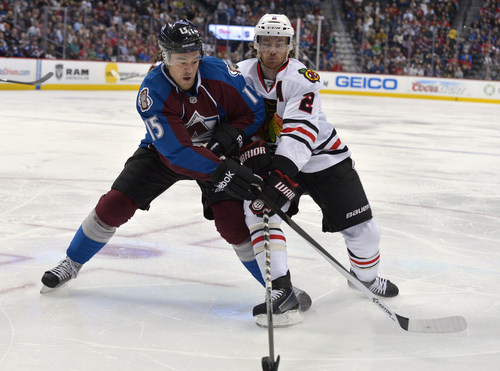 Colorado Avalanche right wing P.A. Parenteau (15) and Chicago Blackhawks defenseman Duncan Keith (2) chase the puck into the corner during the second period of an NHL hockey game Tuesday, Nov. 19, 2013, in Denver. (AP Photo/Jack Dempsey)