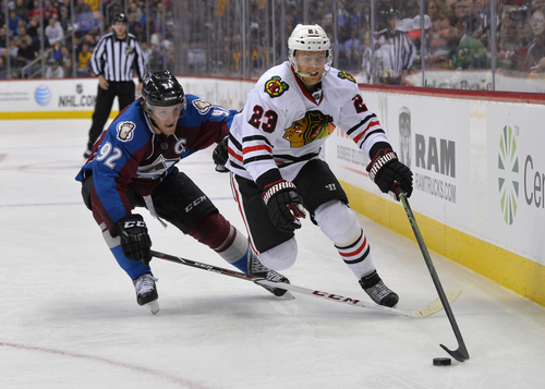 Colorado Avalanche left wing Gabriel Landeskog (92) from Sweden and Chicago Blackhawks right wing Kris Versteeg (23) chase the puck into the corner during the second period of an NHL hockey game Tuesday, Nov. 19, 2013, in Denver. (AP Photo/Jack Dempsey)
