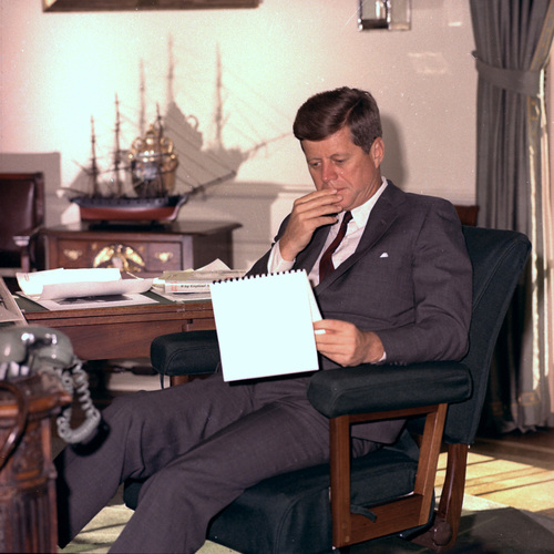 FILE - In this Jan. 18, 1962 file photo, U.S. President John F. Kennedy looks over notes at his desk in the White House. (AP Photo/Henry Burroughs)