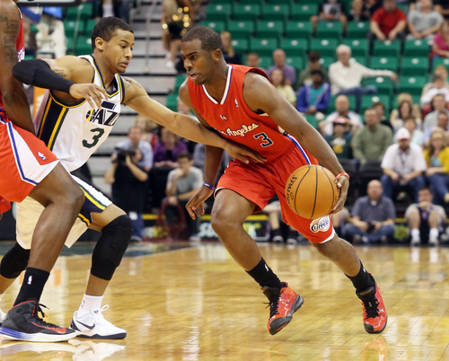 Los Angeles Clippers' Chris Paul, right, dribbles past Utah Jazz's Trey Burke in the first quarter during an NBA preseason basketball game on Saturday, Oct. 12, 2013, in Salt Lake City. (AP Photo/Kim Raff)