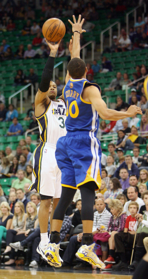 Steve Griffin  |  The Salt Lake Tribune  Utah's Trey Burke makes a three-pointer over Golden State's Seth Curry during first half action in the Jazz versus Golden State preseason NBA basketball game at the EnergySolutions Arena in Salt Lake City, Utah Tuesday, October 8, 2013.